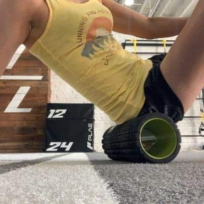 female runner foam rolling in gym close up shot