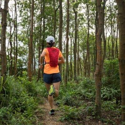 female enjoying running alone in woods