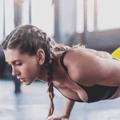 female runner with braids strength training with push ups